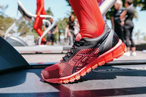 An ASICS red running shoe on a treadmill.