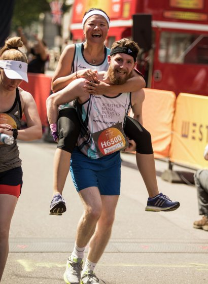 Two runners, one carrying the other on their back at the British 10k Virgin Sport